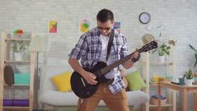 Músico del hombre joven del retrato con los vidrios que tocan emocionalmente la guitarra eléctrica almacen de metraje de vídeo