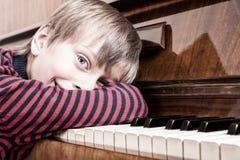Músico divertido hermoso del niño que juega la sonrisa del piano Fotografía de archivo