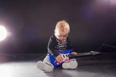 Músico do rapaz pequeno que joga a música rock na guitarra imagens de stock royalty free