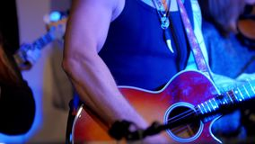 Músico en el concierto de rock - los guitarristas tocan la guitarra acústica roja en club de noche metrajes
