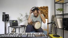 Músico en el estudio casero de la música que pone los auriculares y la prueba almacen de metraje de vídeo