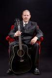 Músico en el traje de negocios que se sienta en la silla roja del terciopelo que sostiene la guitarra Fotos de archivo libres de regalías