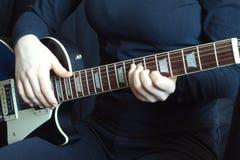 Músico en jugar negro en la guitarra eléctrica Foto de archivo libre de regalías