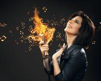 Músico fêmea da rocha que entrega o mic de queimadura imagens de stock