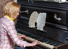 Músico fêmea de sorriso que joga a partitura no piano retro fotografia de stock royalty free