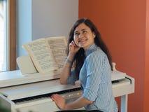 Músico fêmea feliz que joga o piano interno Imagens de Stock Royalty Free