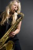 Músico fêmea louro 'sexy' do jogador de saxofone imagem de stock