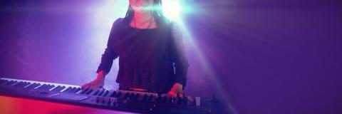 Músico fêmea que joga o piano no clube iluminado imagem de stock royalty free