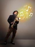 Músico hermoso que juega en el saxofón con las notas musicales Foto de archivo libre de regalías