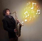 Músico hermoso que juega en el saxofón con las notas musicales Imágenes de archivo libres de regalías