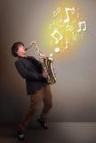 Músico hermoso que juega en el saxofón con las notas musicales Fotos de archivo