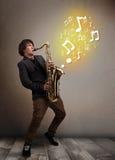 Músico hermoso que juega en el saxofón con las notas musicales Fotografía de archivo