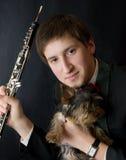 Músico joven con el perro de Yorkshire. Foto de archivo