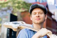 Músico joven con la guitarra en ciudad Fotografía de archivo libre de regalías