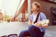 Músico joven con la guitarra en ciudad Fotografía de archivo
