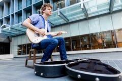 Músico joven con la guitarra en ciudad Foto de archivo libre de regalías