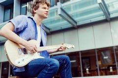 Músico joven con la guitarra en ciudad Imagen de archivo