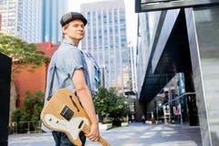 Músico joven con la guitarra en ciudad Fotos de archivo libres de regalías