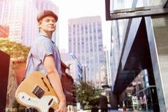 Músico joven con la guitarra en ciudad Fotos de archivo