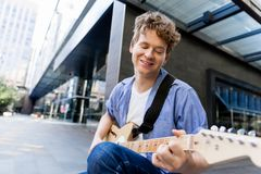 Músico joven con la guitarra en ciudad Foto de archivo