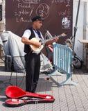 Músico joven de la calle que toca el laúd en la costa Foto de archivo libre de regalías