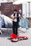 Músico joven de la calle que toca el laúd en la costa Fotos de archivo libres de regalías
