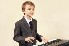 Músico joven del principiante en el traje que juega el órgano electrónico Fotografía de archivo