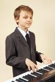 Músico joven del principiante en el traje que juega el piano digital Fotografía de archivo libre de regalías