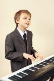 Músico joven del principiante en el traje que juega el sintetizador Imagen de archivo libre de regalías