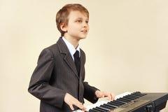 Músico joven del principiante en el traje que juega el synth electrónico Imagen de archivo
