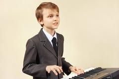 Músico joven del principiante en un traje que juega el piano electrónico Fotografía de archivo
