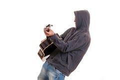 Músico joven en la sudadera con capucha negra que juega la guitarra y la danza Imagen de archivo libre de regalías