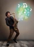 Músico joven que juega en el saxofón mientras que explodin de las notas musicales Imagen de archivo