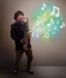 Músico joven que juega en el saxofón mientras que explodin de las notas musicales Imagenes de archivo