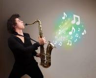 Músico joven que juega en el saxofón mientras que explodin de las notas musicales Imagen de archivo libre de regalías