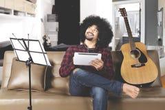 Músico joven que piensa con la tableta digital Foto de archivo libre de regalías