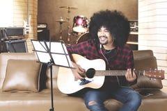 Músico joven que toca la guitarra en estudio de la música Fotos de archivo