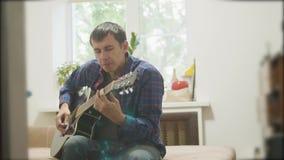 músico masculino que joga a guitarra acústica equipe o jogo do vídeo de movimento lento acústico da guitarra do estilo de vida na video estoque