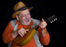 Músico mayor con la mandolina que juega y música country del canto Foto de archivo libre de regalías