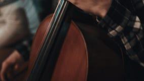 Músico novo com o rabo de cavalo na camisa de manta que joga o violoncelo com arco video estoque