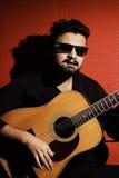 Músico novo considerável que joga a guitarra e que canta Foto de Stock Royalty Free