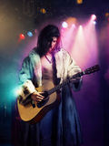 Músico novo da rocha no casaco de pele que joga a guitarra no concerto Foto de Stock