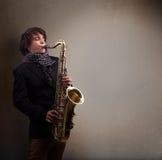 Músico novo que joga no saxofone Fotos de Stock
