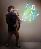 Músico novo que joga no saxofone quando explodin das notas musicais Fotos de Stock