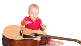 Músico pequeno bonito que joga a guitarra no fundo branco Fotografia de Stock