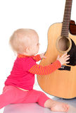 Músico pequeno bonito que joga a guitarra no fundo branco Imagem de Stock