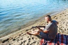 Músico por el agua Imagenes de archivo