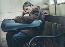 Músico que duerme en su instrumento en banco de la calle