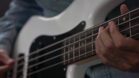 M?sico que joga a guitarra-baixo com a picareta no est?dio filme