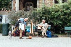 Músico que joga a guitarra e a harpa nas ruas de Bruges foto de stock